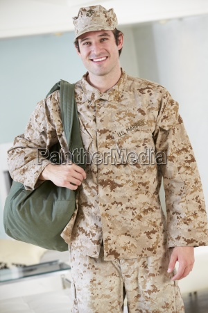 male soldier with kit bag home