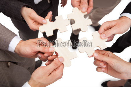 business people fixing jigsaw pieces