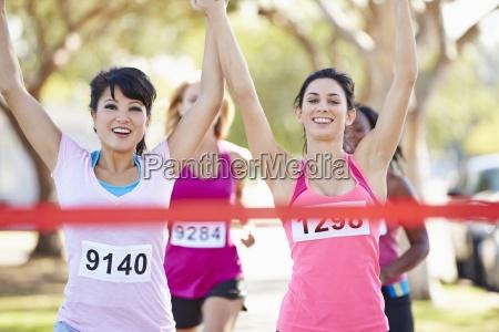 zwei weibliche laeufer finishing rennen zusammen