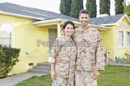 military couple in uniform standing outside