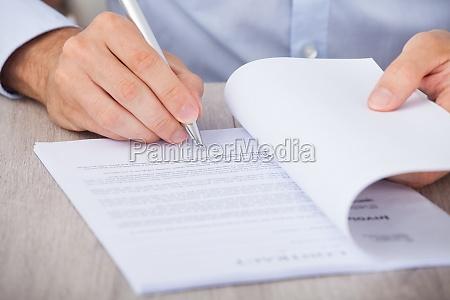 geschaeftsmann unterschreibt vertrag am schreibtisch
