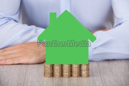 businessman with green house model on