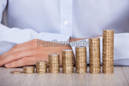 businessmans hand behind euro coins at