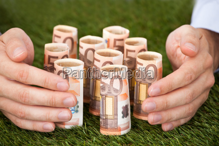 hands protecting euro notes on grass