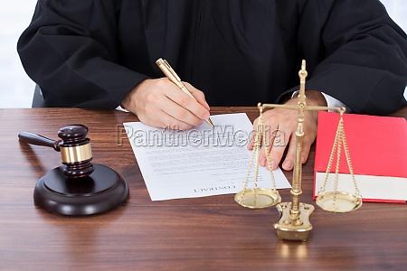 judge unterschreiben vertrag papier am schreibtisch