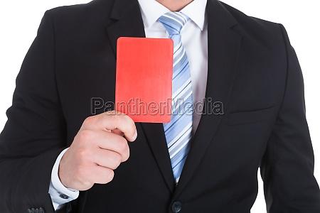 geschaeftsmann der rote karte zeigt
