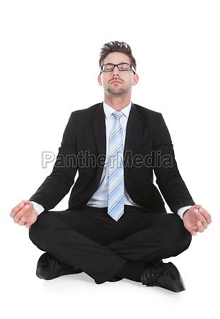 geschaeftsmann meditingiert ueber weissen hintergrund