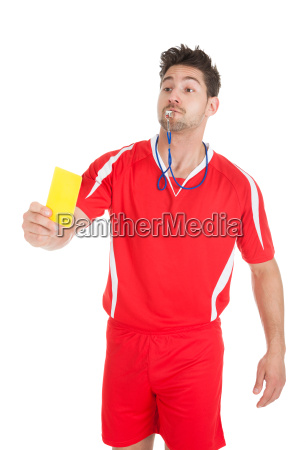 schiedsrichter blowing whistle beim zeigen gelbe