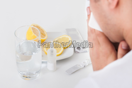 man suffering from cold with medicines