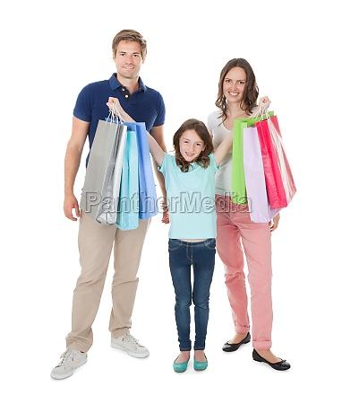 portraet der gluecklichen familie mit einkaufstaschen