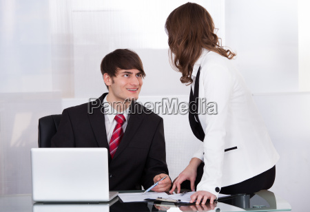businessman looking at female colleague while