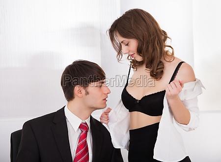 businesswoman undressing self to seduce boss