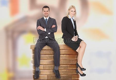geschäftsleute, sitzen, auf, gestapelte, münzen - 12543026