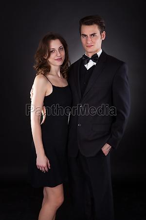 elegant couple standing over black background
