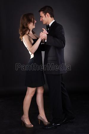 elegant couple dancing over black background