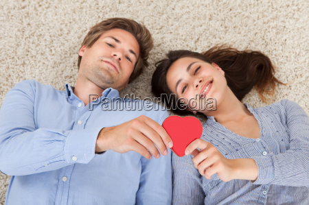 couple holding heart while lying on