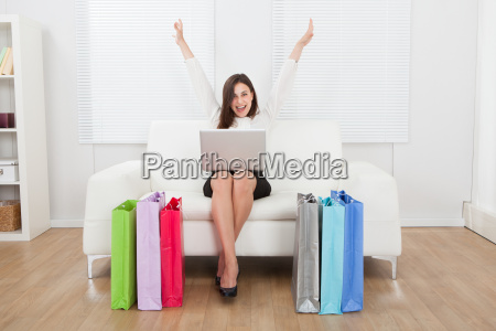 excited businesswoman with laptop shopping online