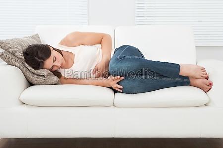 frau leidet an magenschmerzen auf sofa
