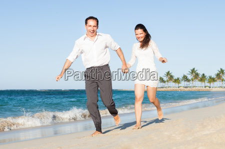 happy couple holding hands while running