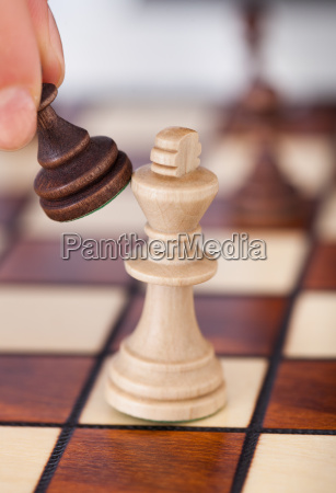 womans hand playing chess