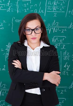 confident teacher standing arms crossed