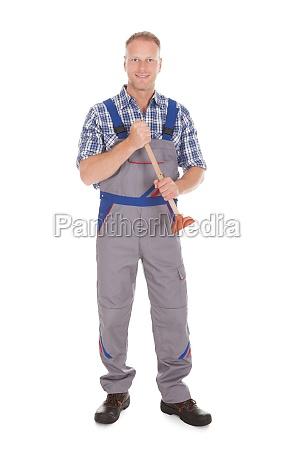 aufgeregt junge maennliche plumber holding plunger
