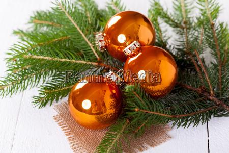 glaenzende orangene glaskugeln weihnachtskugeln mit gruenen