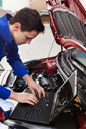 mechaniker mit laptop beim reparieren auto