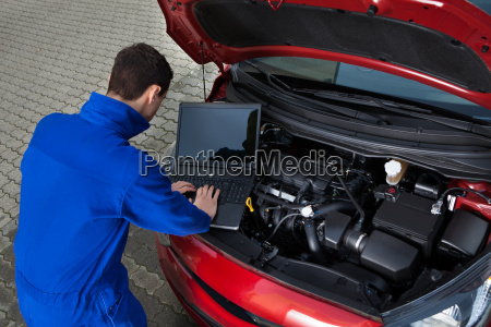 mechaniker laptop waehrend auto reparieren