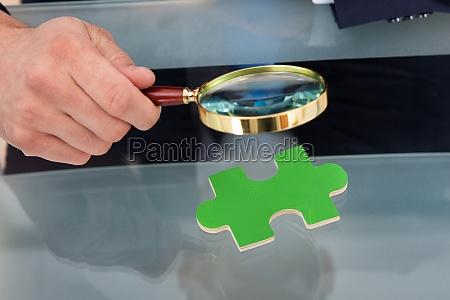 geschaeftsmann scrutinizing puzzleteil mit lupe