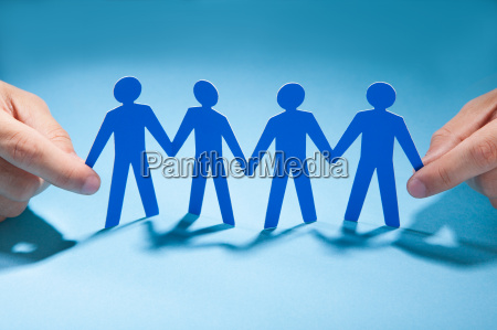 businessmans hands holding paper people chain