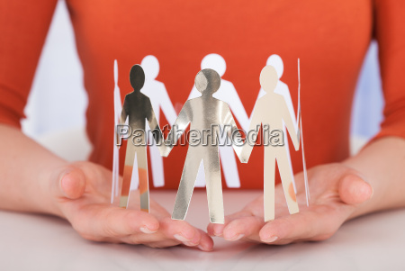 businesswoman holding team of paper people