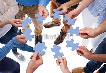 gruppe von menschen die puzzleteile verbinden
