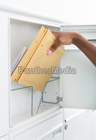 woman getting letters from mailbox