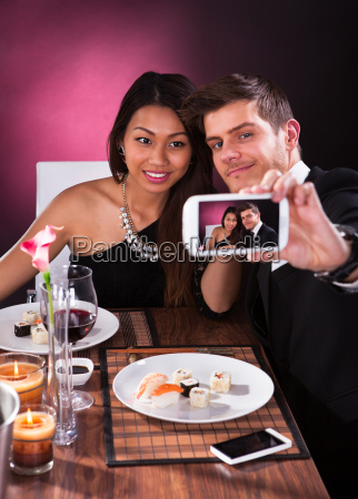 couple taking self portrait at restaurant