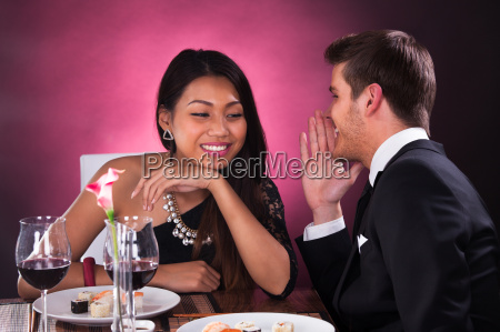 man whispering in womans ear at
