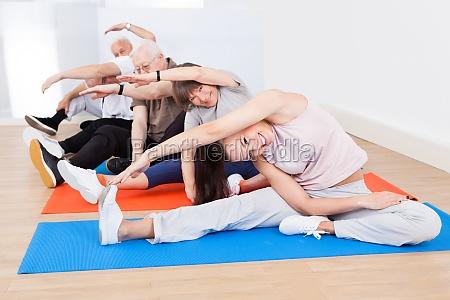 trainer und aeltere kunden yoga tun