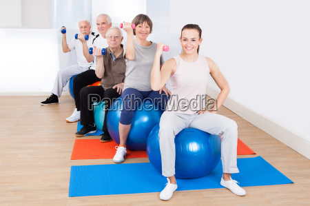 people using hand weights while sitting