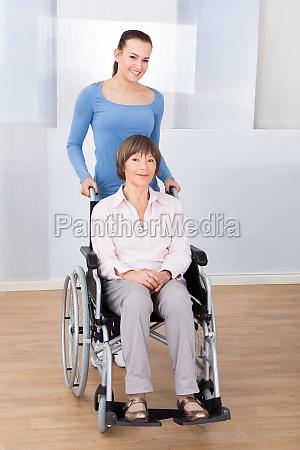 caregiver mit behinderten aelteren frau im