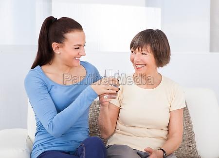 caregiver giving glas wasser um aeltere