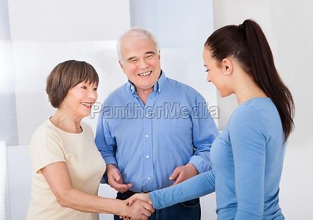 caregiver haendeschuetteln mit seniorenpaar