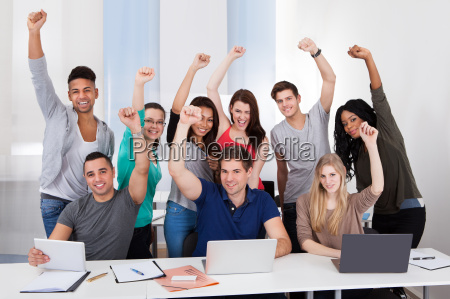 happy college students celebrating success in