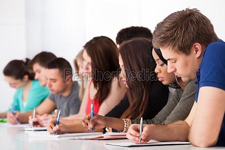 reihe von studenten schreiben am schreibtisch