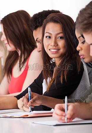 female student sitting with classmates writing