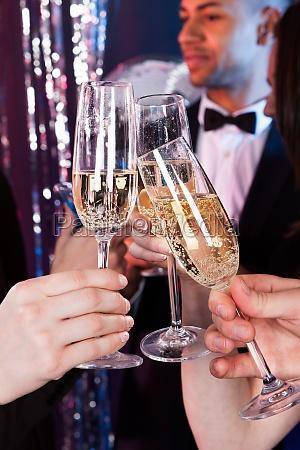 freunde toasten champagner im nachtclub