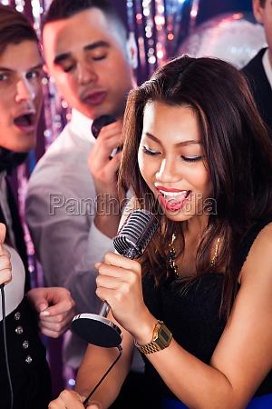 frau singen into mikrofon bei karaoke