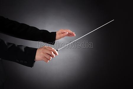 weiblicher orchester dirigent mit taktstock