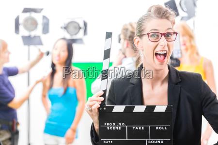 frau mit filmklappe bei produktion am