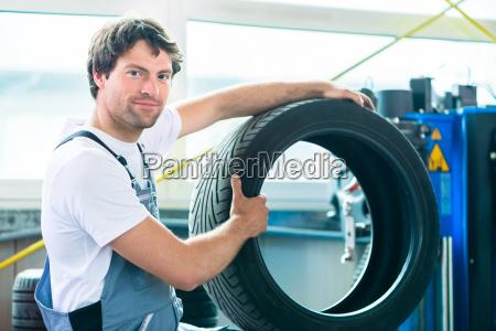 mechanics at changing tires in garage