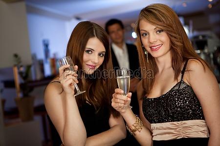 two young women drinking chanpagne